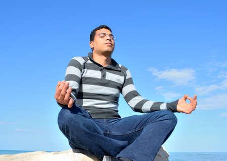 Young arab man meditating at the beach in tunisia.