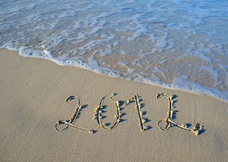 Numbers 2012 written in sand at beach. Concept for new years eve. photo