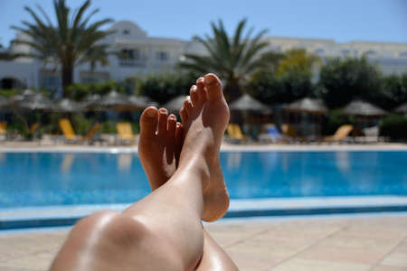Legs of young woman relaxing at tropical pool. Stock Photo
