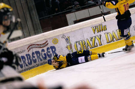 ZELL AM SEE, AUSTRIA - FEB 22: Austrian National League. Stefan Uhl injured after a cheap shot by Remi Royer. Game EK Zell am See vs. VEU Feldkirch (Result 3-1) on February 22, 2011 at hockey rink of Zell am See