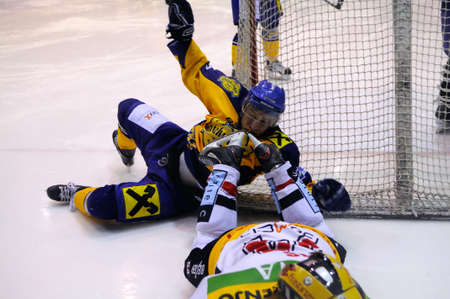 bodycheck: ZELL AM SEE, AUSTRIA - FEB 22: Austrian National League. Stefan Uhl gets caught by the skates of VEU player. Game EK Zell am See vs. VEU Feldkirch (Result 3-1) on February 22, 2011 at hockey rink of Zell am See
