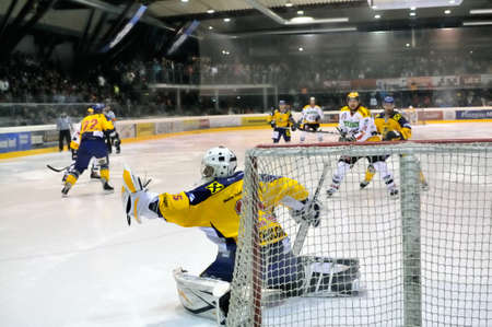 bodycheck: ZELL AM SEE, AUSTRIA - FEB 22: Austrian National League. Goalie Bartholomaus saves the puck. Game EK Zell am See vs. VEU Feldkirch (Result 3-1) on February 22, 2011 at hockey rink of Zell am See