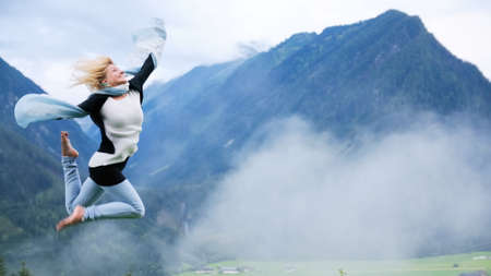 freedom leisure activity: Young beautiful woman jumping at mountain