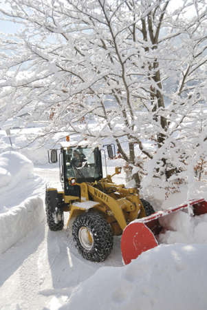 loader: INNSBRUCK; AUSTRIA - JAN 8: Snow removal vehicle removing snow after blizzard in Tirol, Austria which caused several damages.