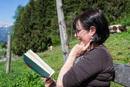 Aged Woman sitting on bench in rural nature landscape relaxing and reading a book  photo