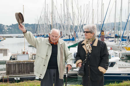 elderly french couple walking together at the yacht harbor of brest in brittany Stock Photo