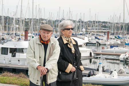 elderly french couple walking together at the yacht harbor of brest in brittany photo