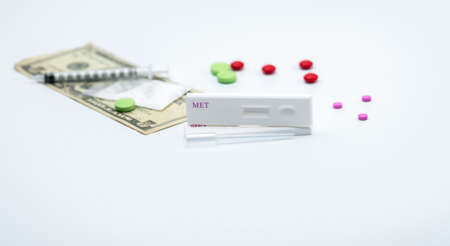 Two methamphetamine cassette test and plastic dropper with red, pink and green drugs, fake heroin powders, american dollar bills and syringe and needle on white background with copy space