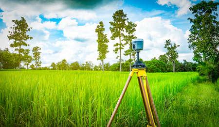 緑の水田、タイの三脚に GPS 測量計器のインストール