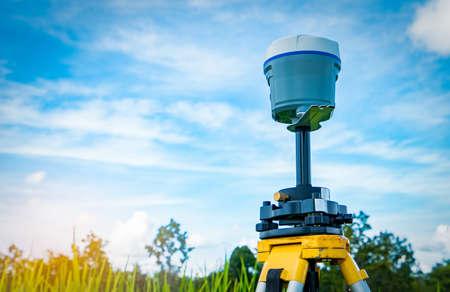 青い空と田んぼの背景に GPS 測量計器