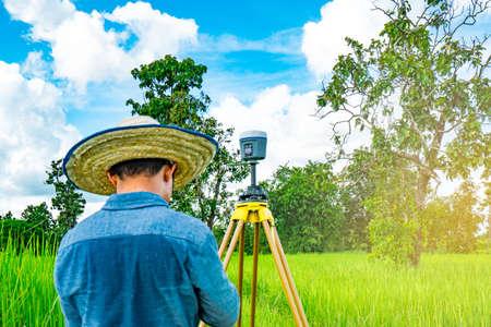 아시아 스마트 엔지니어 또는 검정 청바지와 긴 소매 셔츠와 짠 대나무 모자에서 측량 자. 그는 태국의 논에서 토지를 측량하는 컨트롤러 스크린에서