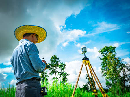 Asian smart engineer or surveyor in black jeans and long sleeve shirt and woven bamboo hat. He is working on controller screen for surveying land in rice field, Thailand. GPS surveying instrument.