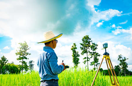 he: Asian smart engineer or surveyor in black jeans and long sleeve shirt and woven bamboo hat. He is working on controller screen for surveying land in rice field, Thailand. GPS surveying instrument.