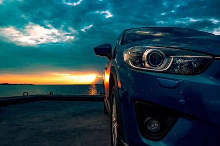 Blue compact SUV car with sport and modern design parked on concrete road by the sea at sunset. Environmentally friendly technology. Business success concept. Stock Photo