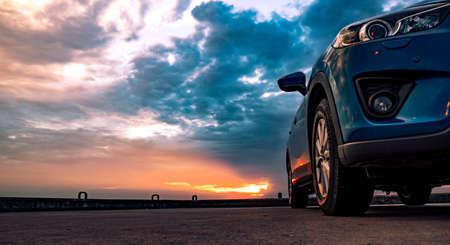 夕暮れ時、海によるコンクリート舗装にスポーツとモダンなデザインとブルーのコンパクト SUV 車を止めた。環境に優しい技術です。ビジネスの成功 写真素材