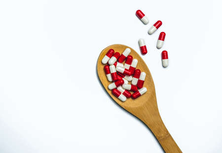Colorful of antibiotics capsule pills in wooden spoon are spilling on white background with copy space. Antibiotic drug use with reasonable and health insurance concept.