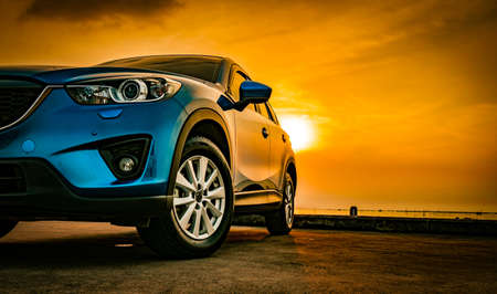 Blue compact SUV car with sport and modern design parked on concrete road by the sea at sunset. Environmentally friendly technology. Business success concept. Foto de archivo