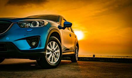 Voiture compacte bleue de SUV avec le sport et la conception moderne garée sur la route concrète par la mer au coucher du soleil. Technologie respectueuse de l'environnement. Concept de succès commercial. Banque d'images