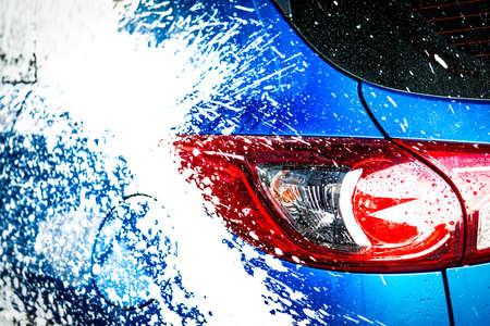 Hintere Ansicht des blauen kompakten SUV-Autos mit dem Sport und modernem Design, die mit Seife sich waschen. Auto mit weißem Schaum bedeckt. Autopflegeservice-Geschäftskonzept.