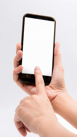 Close-up hand touching smartphone screen isolated on white background with clipping path and copy space for text, mock up mobile phone with blank screen. Foto de archivo