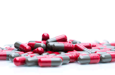 Macro shot detail selective focus of red and grey capsule pills isolated on white background with copy space for text. Migraine prophylaxis medicine