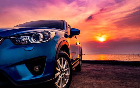 Voiture compacte bleue de SUV avec le sport et la conception moderne garée sur la route concrète par la mer au coucher du soleil. Technologie respectueuse de l'environnement. Concept de succès commercial.