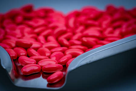 Macro shot detail of red kidney shape sugar coated tablet pills on stainless steel drug tray