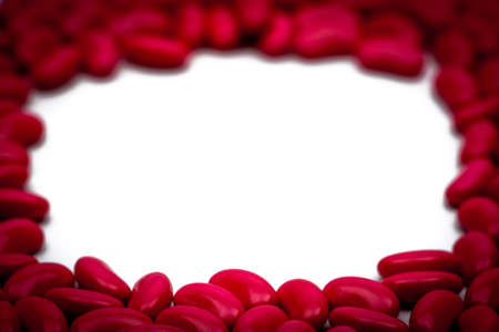 Selective focus of red kidney shape sugar coated tablet pills on white background with copy space Stock Photo