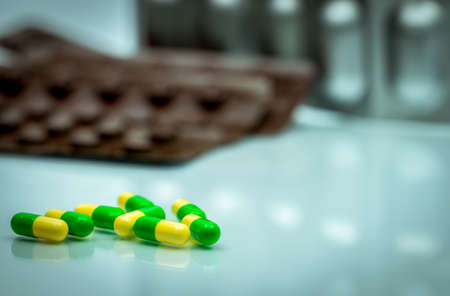 Green, yellow tramadol capsule pills on blurred blister pack background with copy space. Cancer pain management. Opioid analgesics. Drug abuse in teenage in Thailand. Фото со стока