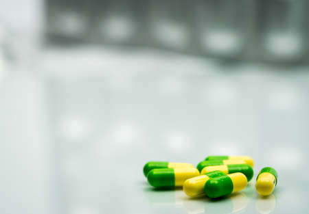 Green, yellow tramadol capsule pills on blurred silver blister pack background with copy space. Cancer pain management. Opioid analgesics. Drug abuse in teenage Stock Photo