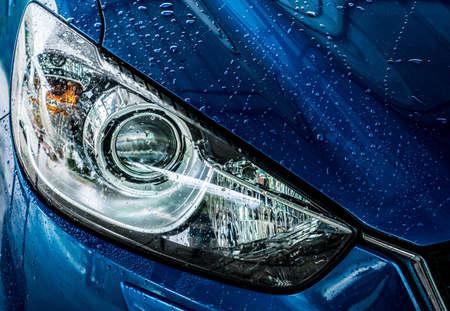 スポーツとモダンなデザインのブルーコンパクトSUVカーが水洗い。カーケアサービス事業コンセプト。高圧水噴霧で洗浄した後、水滴で覆われた車