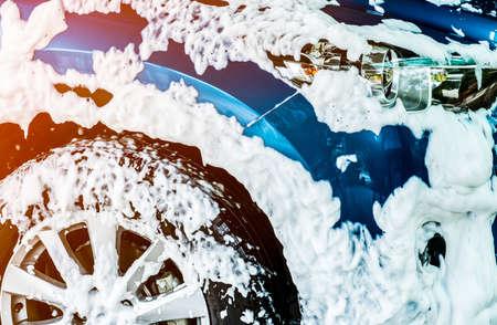 Blauwe compacte SUV-auto met sport en modern design wassen met zeep. Auto bedekt met wit schuim. Auto zorg service bedrijfsconcept.
