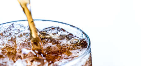 Closeup of soft drink pouring to glass with ice isolated on white background with copy space.