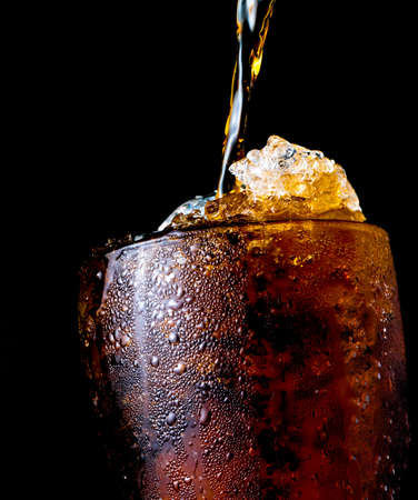 Soft drink pouring to glass with ice isolated on dark background Stock Photo