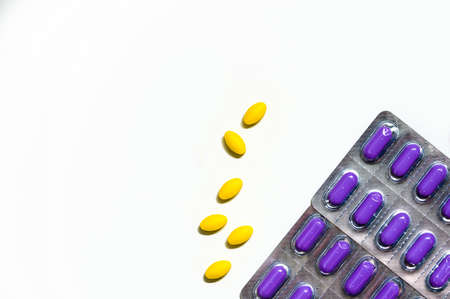 Macro shot of yellow oval tablet pills on white background and purple caplets pills in blister pack. Mild to moderate pain management. Pain killer medicine. Paracetamol and ibuprofen tablet pills.