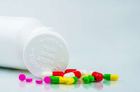 Colorful pills on white background and plastic bottle with blank label and copy space. Childproof packaging. Child resistant pill container. Push down and turn cap.Global healthcare and love concept.