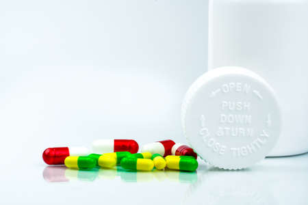 Colorful pills on white background and plastic bottle with blank label and copy space. Childproof packaging. Child resistant pill container. Push down and turn cap.Global healthcare concept. Stock Photo
