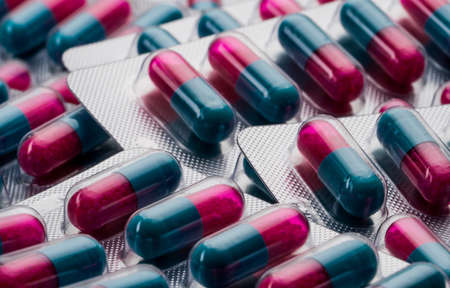 Colorful of blue, pink capsule with granule in side pills. Pills in blister pack. Pharmaceutical dosage form and packaging.