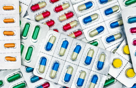 Top view of colorful tablets and capsules pills in blister packs. Global health care and drug use with reasonable concept. Antibiotics resistance concept.