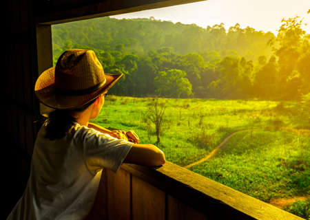 Young Asian woman wear the hat sit and watching beautiful view of green grass field and forest at wildlife observation tower in the evening with warming sunlight. Travel concept.