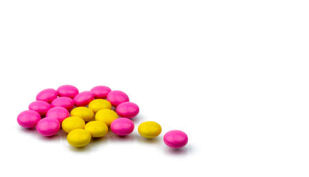 Pile of pink and yellow round sugar coated tablets pills isolated on white background with copy space. Colorful pills for treatment anti-anxiety, antidepressant and migraine headache prophylaxis. Stock Photo