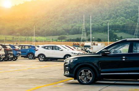 Zwart, wit en blauw nieuwe auto geparkeerd op betonnen parkeerplaats in de fabriek in de buurt van de berg. Autodealer concept. Auto voorraad te koop. Autofabriek parkeerplaats. Auto-industrie concept.