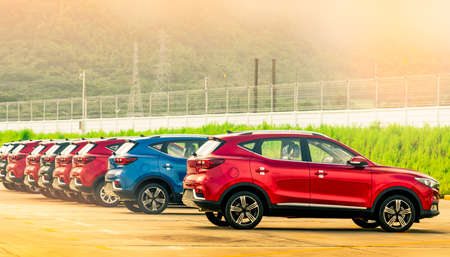 Luxury red, blue and black new suv car parked on concrete parking area at factory near fence of factory. Car stock for sale. Car factory parking lot. Automotive Industry concept. Car dealership.