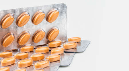 Orange oval tablet pills isolated on white background. Medicine for treating venous circulation disorders (swollen legs, pain, restless legs) and hemorrhoids and acute hemorrhoidal attack.