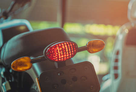 Motorcycle break and turn signal light on blurred background. New big bike park in showroom. Motorbike dealership concept. Parts of motorcycle. Motorcycle license test concept. 스톡 콘텐츠