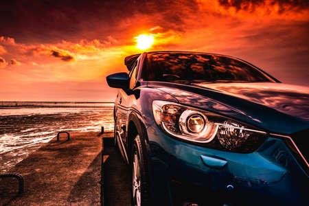Voiture SUV compact bleu avec design sport, moderne et luxueux garée sur une route en béton au bord de la mer au coucher du soleil Vue de face de la belle voiture hybride. Conduire en toute confiance. Voyagez en vacances à la plage.