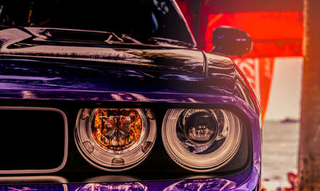 Closeup headlight lamp of purple classic vintage car on blurred red background.