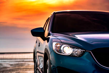 Blue compact SUV car with sport and modern design parked on the beach by the sea at sunset. Environmentally friendly technology. Business success concept. Front view car with open headlamp light.