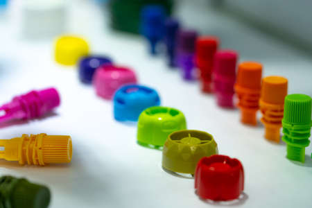 Selective focus on different type of plastic bottle cap of food and drink product. Green, yellow, red, pink, orange, blue, and purple cap closure on white table. Modern design plastic bottle cap. Imagens