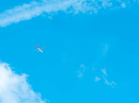 Airplane on blue sky and white clouds. Commercial airline flying on blue sky. Travel flight for vacation. Aviation transport. Travel on vacation by plane.